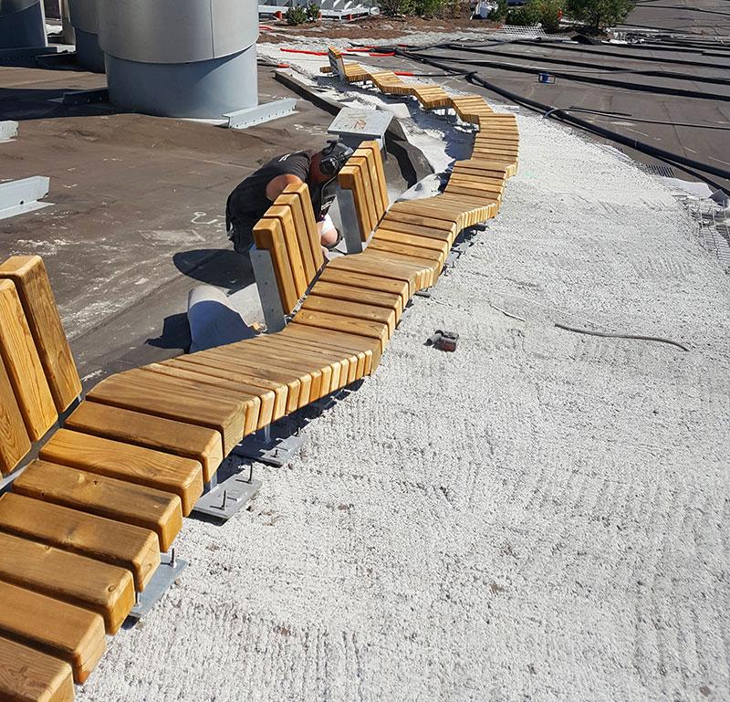 In das Betonfundament können allerlei Aufbauten verankert werden – wie diese originelle und fast endlose Holzbank. Quelle: Malmos A/S / ZinCo