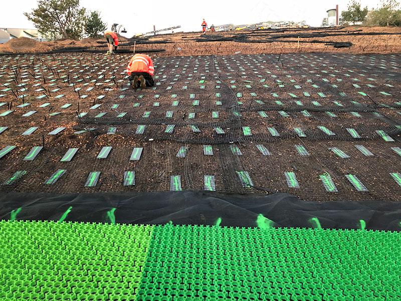 Teilabschnitt um Teilabschnitt wird das Kunststoffnetz fixiert und im Anschluss die grünen Kunststoffmatten auf den Metallplatten verschraubt. Quelle: Malmos A/S / ZinCo