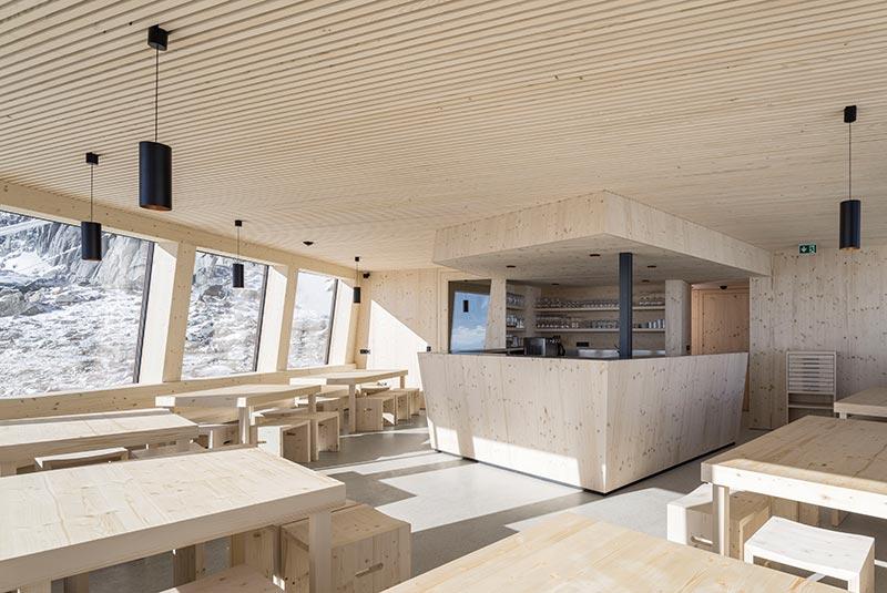 Im lichtdurchfluteten Essbereich gewährt ein durchgehendes Fensterband den Gästen einen 180-Grad-Panoramablick auf die Bergwelt. Im Barbereich erkennt man das Velux Fenster, durch das die Gäste auf der Terrasse bedient werden können. Foto: Velux / Stifter + Bachmann / Oliver Jaist